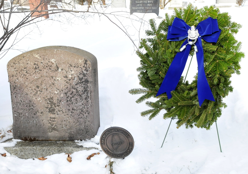 FIRST FATALITY: The gravesite of Trooper Emery Gooch was cleared and a wreath placed on it by fellow troopers at the Pine Grove Cemetery in Waterville on Tuesday. Gooch was the first officer of the Maine State Police to die in the line of duty, in 1924.