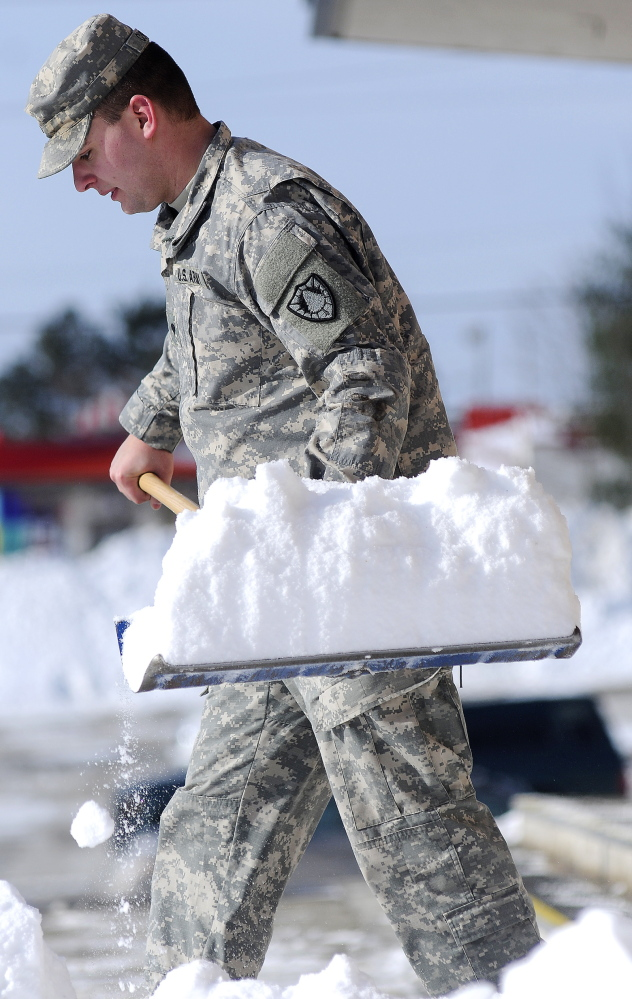 CLEAR THE DECKS: Maine Army National Guard Specialist Daniel Curtis, 21, removes snow Tuesday from the steps of the Augusta State Armory, a day before the newest round of snow.