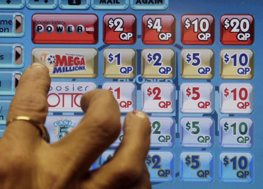 A clerk prepares to operate a lottery machine to print out Mega Millions lottery tickets for a customer at Tobacco Plus, in Muncie, Ind., Tuesday.