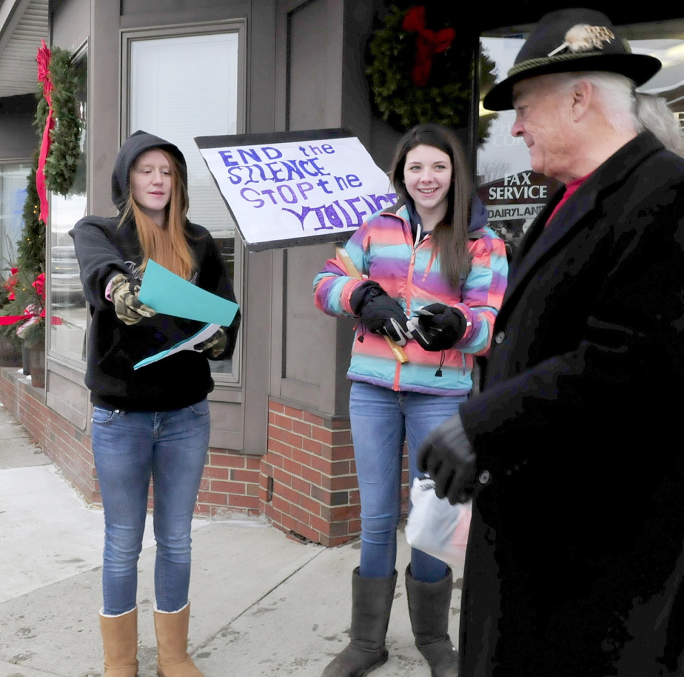 READ THIS: Mt. Blue High School students Tashia Berkey, left, and Cassie Ross distribute information about sexual violence during a silent demonstration on Main Street in Farmington on Thursday. Passerby Robert Underwood took some pamphlets.