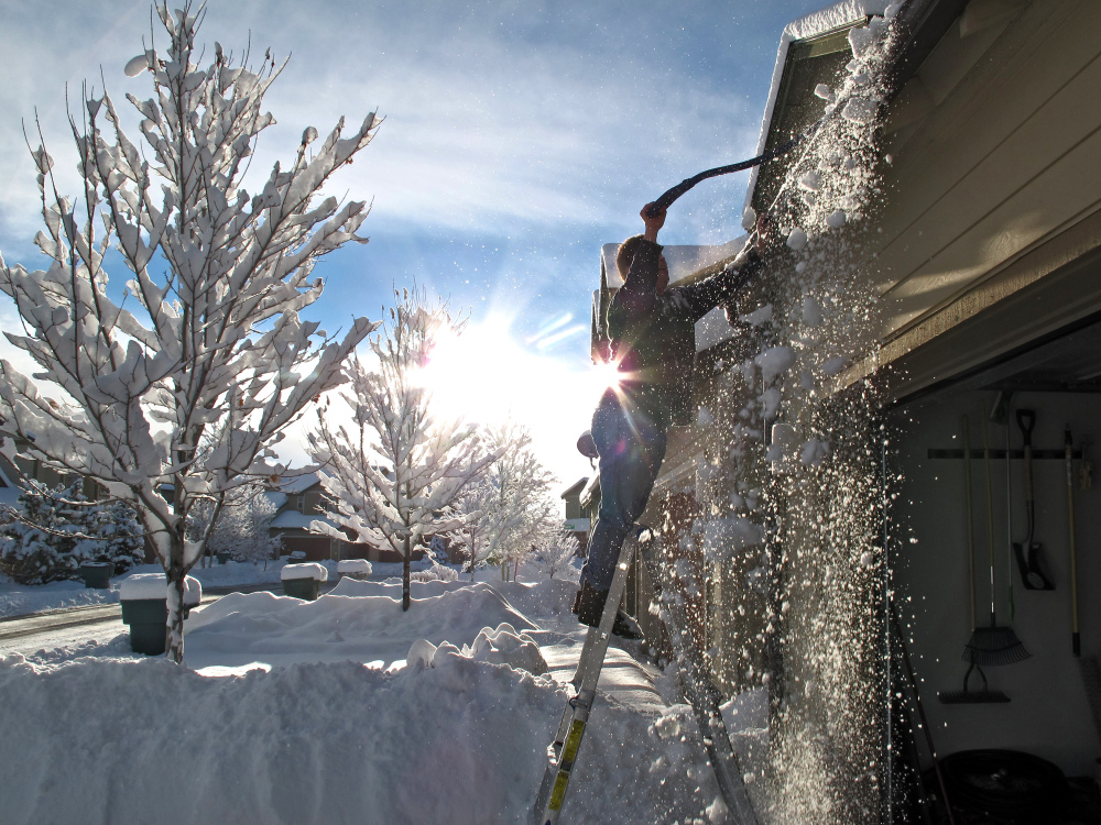 Keola Wong removes snow from the roof of his Bellemont, Ariz., home on Friday. A storm system dropped heavy snow in northern Arizona while Phoenix-area streets and highways were wet from rain during the morning commute.