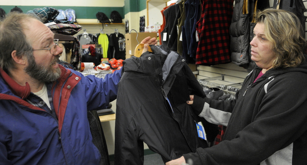 AHEAD OF THE ICE: Jay Lewis discusses the merits of a jacket Friday with his wife, Tracy, at Renys in Gardiner. The couple made a hasty holiday shopping trip in the morning, before having snow tires put on their car in the afternoon in anticipation of an ice storm forecast for this weekend.