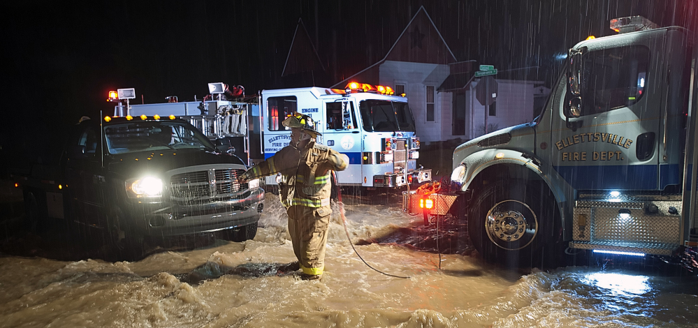 An Ellettsville fire fighter sets up a safety rope as they prepare to wade through moving flood water in Ellettsville, Ind., on Saturday, Dec. 21, 2013. National Weather Service meteorologist Mike Ryan says three to four inches of rain fell between Friday night and Saturday evening on the southwestern Indiana cities of Vincennes and Washington and further east in the Bedford and Bloomington areas. He says the heaviest bands of rain were expected to arrive Saturday night before tapering off early Sunday.