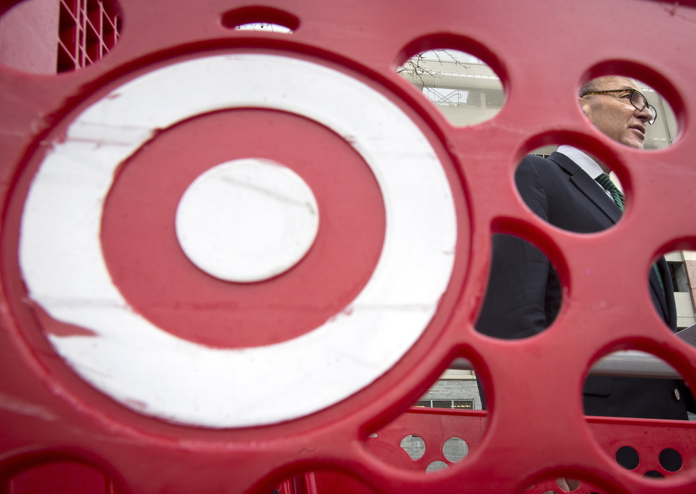 U.S. Sen. Charles Schumer, D-N.Y., pictured through a Target shopping cart, holds a news conference in New York on Sunday about the massive credit card hack that has affected 40 million Target customers.
