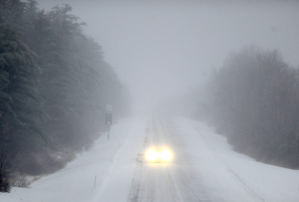 ICEY DICEY: A lone car drives north on Interstate 95 in Waterville as a dangerous wintry mix of ice and snow falls on Sunday morning.