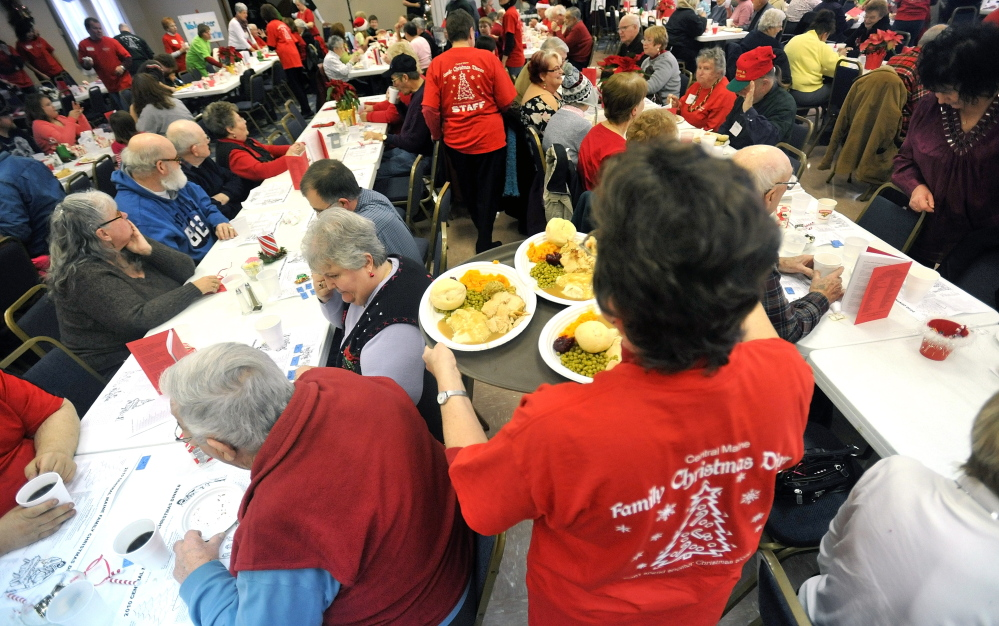 Annual Event: A volunteer delivers meals to people at a previous Central Maine Family Christmas Dinner at the Elks Lodge in Waterville.