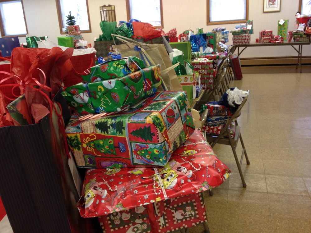 Wishes granted: Presents awaiting pickup by caseworkers for the Maine Department of Health and Human Services line tables at Sacred Heart Parish Hall in Hallowell Monday morning. The presents, largely bought by parishioners of three Hallowell churches, will be given to families in need before Christmas.