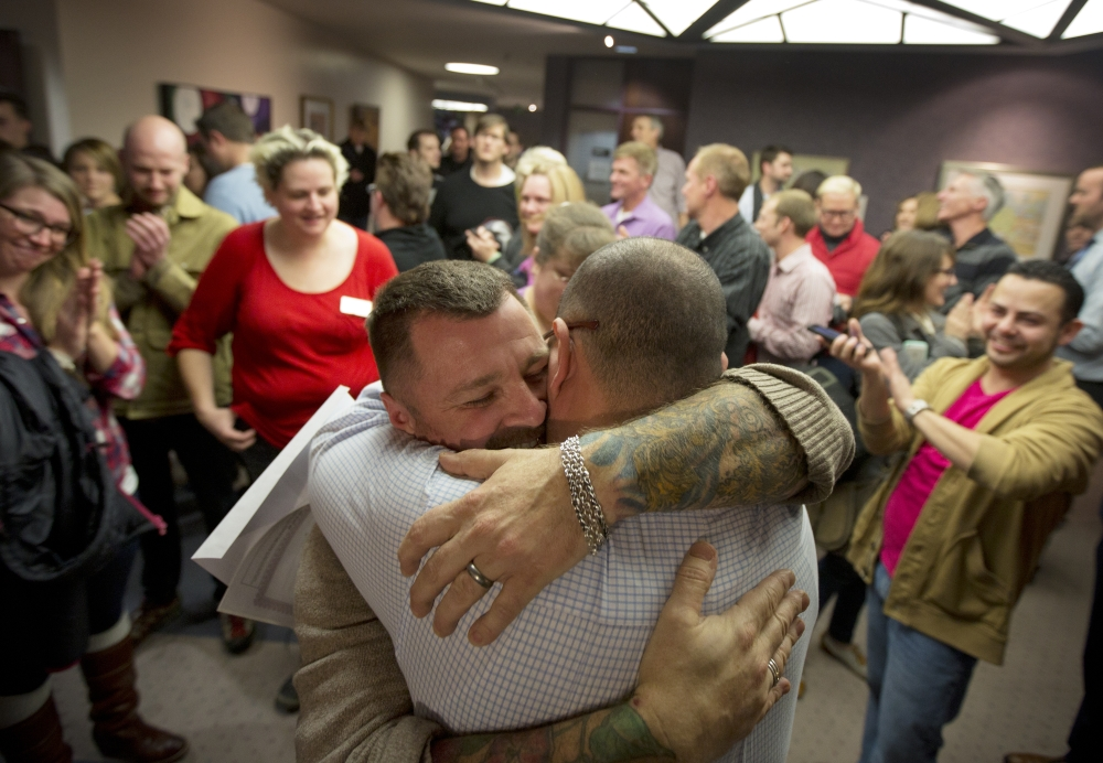 Chris Serrano, left, and Clifton Webb embrace after being married, as people wait in line to get licenses outside of the marriage division of the Salt Lake County Clerk's Office in Salt Lake City. A federal judge is set to consider a request from the state of Utah to block gay weddings that have been taking place since Friday when the state's same-sex marriage ban was overturned.