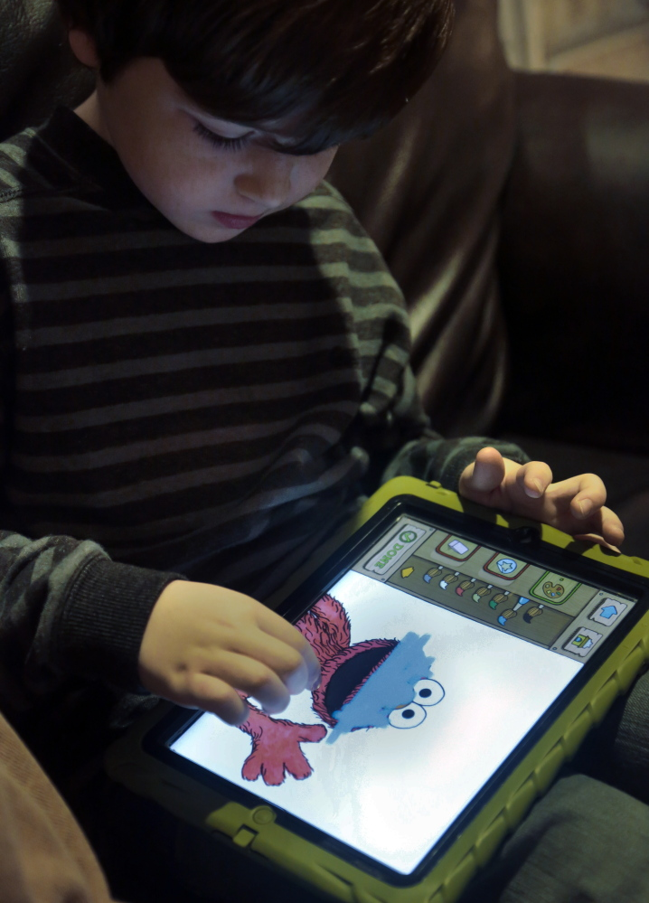 Marc Cohen uses a Sesame Street app on his tablet at home in New York.