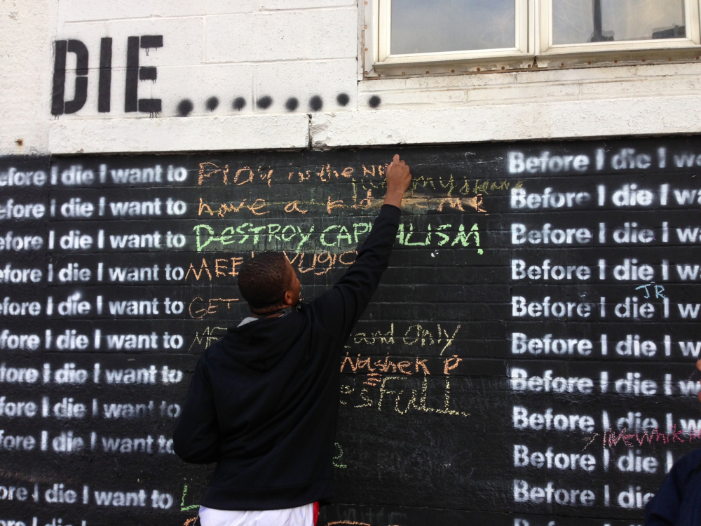 "Nyquis Turner, 16, writes ""Play in the NFL"" on a wall in Syracuse, N.Y., that invites passers-by to complete the sentence: ""Before I die, I want to..."""