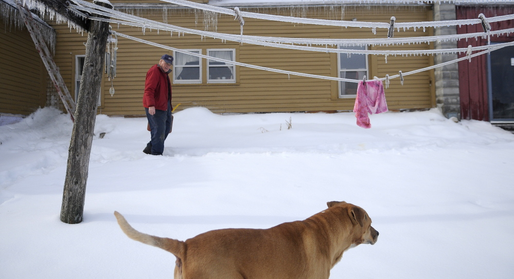 Staff photo by Andy Molloy SHELTER: Sonny Black walks past the frozen clothes line at his Litchfield farm after firing up the generator. Black had purchased a generator a few years ago to permit him to remain at the farm and tend to the herd of beef and dairy cows.