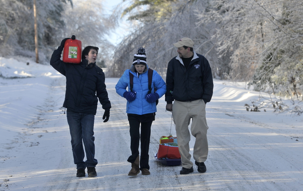 Staff photo by Michael G. Seamans STORM RECOVERY: Chris Devine, far right, hauls a sled of gifts with his daughter Jordan, 11, and step son Derek Gervais, 20, far left, carrying gas for the generator on Maplehurst Lane in Belgrade on Wednesday, Dec. 25, 2013. The Devine's lost power on Monday and haul their supplies in on sled. Trees and power lines are down on both sides of their driveway essentially making it impossible to drive in. Luckily they weren't home when the trees fell during the storm affording them the opportunity to drive to town for gas and other essentials for life off the grid.