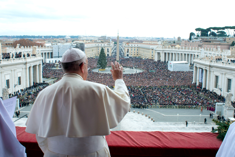 "In this picture provided by the Vatican newspaper L'Osservatore Romano, Pope Francis delivers his ""Urbi et Orbi"" (to the City and to the World) message from the central balcony of St. Peter's Basilica at the Vatican, Wednesday, Dec. 25, 2013. Pope Francis on Christmas day is wishing for a better world, with peace for the land of Jesus' birth, for Syria and Africa as well as for the dignity of migrants and refugees fleeing misery and conflict. Francis spoke from the central balcony of St. Peter's Basilica Wednesday to tens of thousands of tourists, pilgrims and Romans in the square below. He said he was joining in the song of Christmas angels with all those hoping ""for a better world,"" and with those who ""care for others, humbly."""