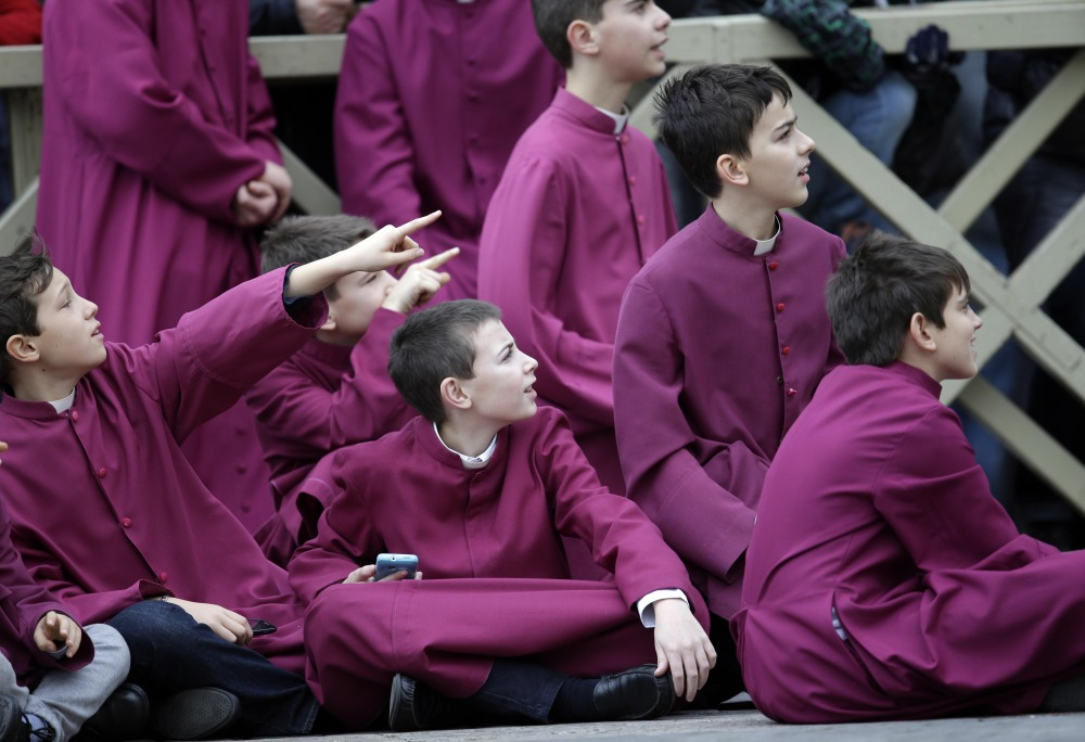 "Altar boys wait for Pope Francis to deliver his ""Urbi et Orbi"" (to the City and to the World) message from the central balcony of St. Peter's Basilica at the Vatican, Wednesday, Dec. 25, 2013. Pope Francis on Christmas day is wishing for a better world, with peace for the land of Jesus' birth, for Syria and Africa as well as for the dignity of migrants and refugees fleeing misery and conflict. Francis spoke from the central balcony of St. Peter's Basilica Wednesday to tens of thousands of tourists, pilgrims and Romans in the square below. He said he was joining in the song of Christmas angels with all those hoping ""for a better world,"" and with those who ""care for others, humbly."""