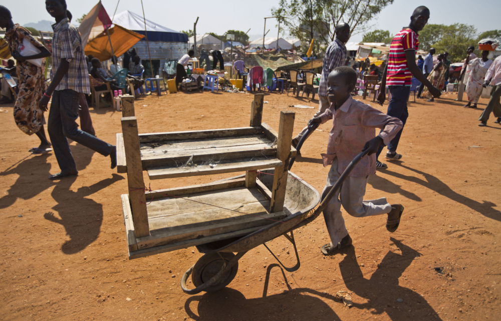 """A displaced boy uses a wheelbarrow to transport belongings inside a United Nations compound which has become home to thousands of people displaced by the recent fighting, in Juba, South Sudan Friday, Dec. 27, 2013. Kenya's president Uhuru Kenyatta on Friday urged South Sudan's leaders to resolve their political differences peacefully and to stop the violence that has displaced more than 120,000 people in the world's newest country, citing the example of the late Nelson Mandela and saying there is """"a very small window of opportunity to secure peace"""" in the country where fighting since Dec. 15 has raised fears of full-blown civil war."""