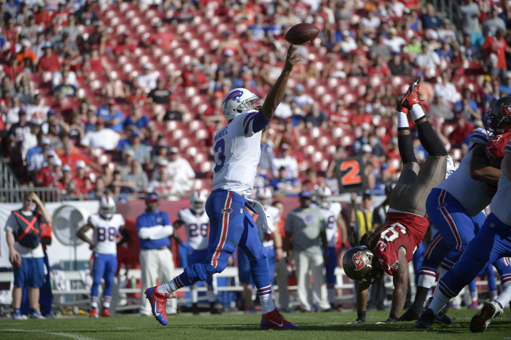 Buffalo Bills quarterback EJ Manuel (3) throws a pass in front of Tampa Bay Buccaneers defensive end Adrian Clayborn (94) during the second half of an NFL football game in Tampa, Fla., Sunday, Dec. 8, 2013.(AP Photo/Phelan M. Ebenhack)