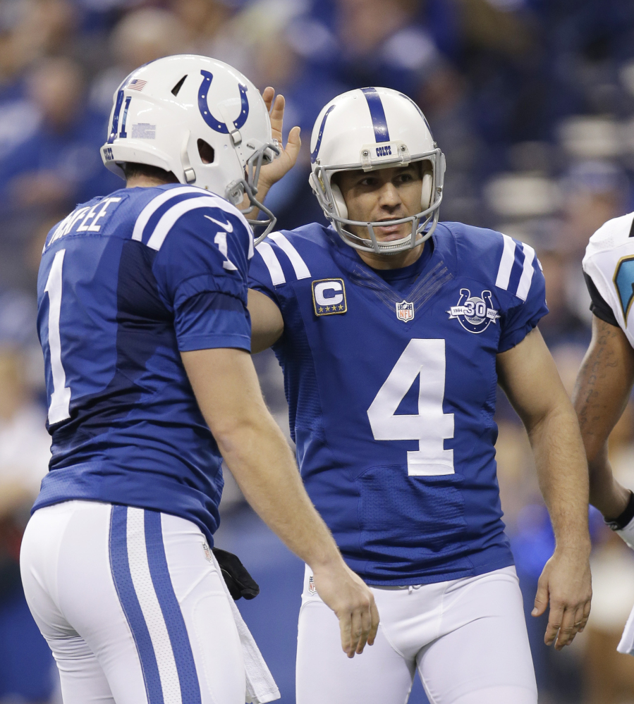 Indianapolis Colts' Adam Vinatieri (4) is congratulated by Pat McAfee (1) after kicking a 23-yard field goal during the first half of an NFL football game against the Jacksonville Jaguars, Sunday, Dec. 29, 2013, in Indianapolis. (AP Photo/AJ Mast)