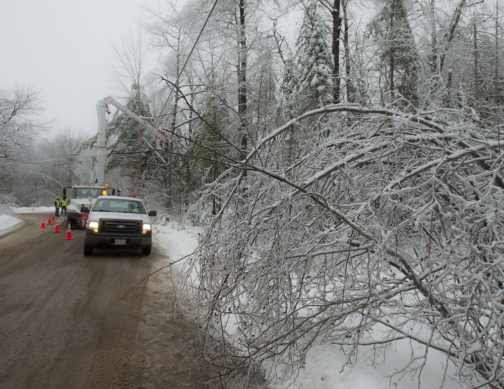 A crew sets up to restore power near Brewer Lake in Orringtonon Sunday. Bangor Hydro line crews working with Asplundh Tree Service crews have been in the King's Mountain area of Orrington since Dec. 26.