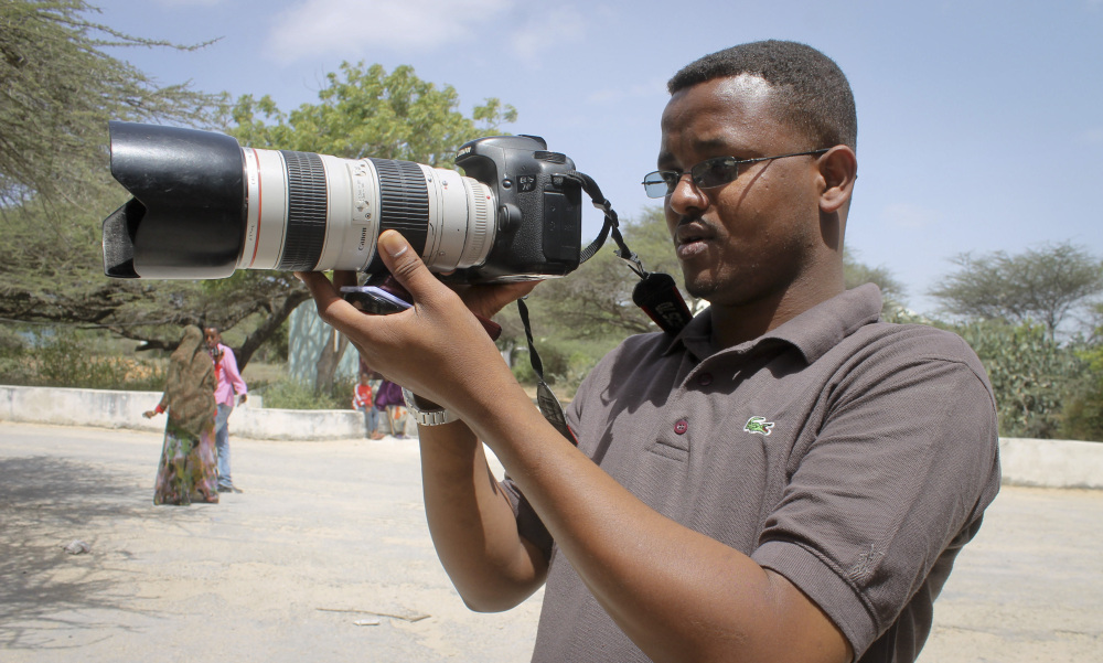 In this photo taken Friday, Jan. 18, 2013, Somali journalist Mohamed Mohamud holds his camera in the Medina hospital compound in Mogadishu, Somalia. Mohamud was among the at least 70 journalists killed on the job around the world in 2013, including 29 who died covering the civil war in Syria and 10 slain in Iraq, according to the Committee to Protect Journalists.