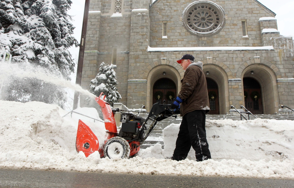 """IN SERVICE OF THE CHURCH: Rich Garling of Waterville works to clear snow from Sunday night's snow in front of Sacred Heart Catholic Church on Pleasant Street in Waterville on Monday. """"This would be normal back in the day. Old Man Winter has returned,"""" said Garling, referring to all the snow that's fallen this month."""
