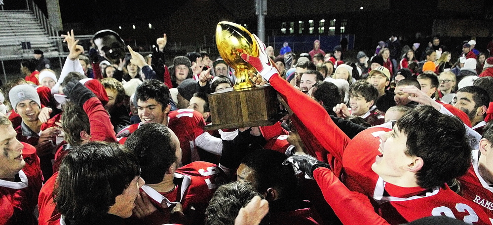 Staff photo by Joe Phelan Cony Rams players and their fans celebrate with gold ball trophy after beating Kennebunk to win the state class B football championship game on Friday November 22, 2013 in Orono.