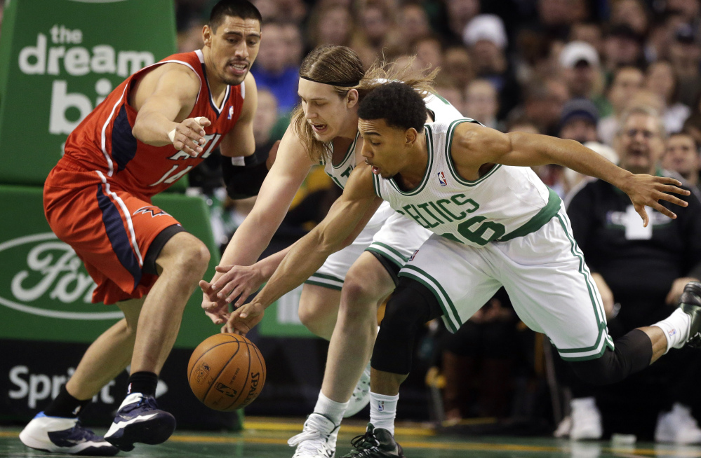 Atlanta Hawks forward Gustavo Ayon, left, and Boston Celtics center Kelly Olynyk, center, and guard Phil Pressey chase a loose ball in the second quarter of an NBA basketball game Tuesday in Boston.