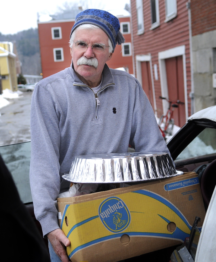 HELPING HAND: Jack Walsh carries a dinner to a customer's car recently at the Hallowell Food Bank, where he volunteers.