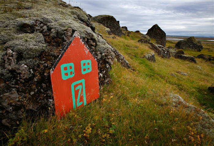 An elf door leans against a rock in the Icelandic countryside outside the village of Selfoss. Belief in the unseen runs so high in Iceland that the Public Roads Administration sometimes delays or reroutes road construction to avoid what locals believe are elf habitations or cursed spots.