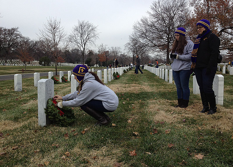 Alexia Fornaro of Portland lays a wreath against a grave at Arlington National Cemetery in Virginia on Saturday as her sister and mother, Daniela and Giulia, look on. The family traveled to Arlington as part of a group from Cheverus High School participating in the Wreaths Across America ceremonies on Saturday.