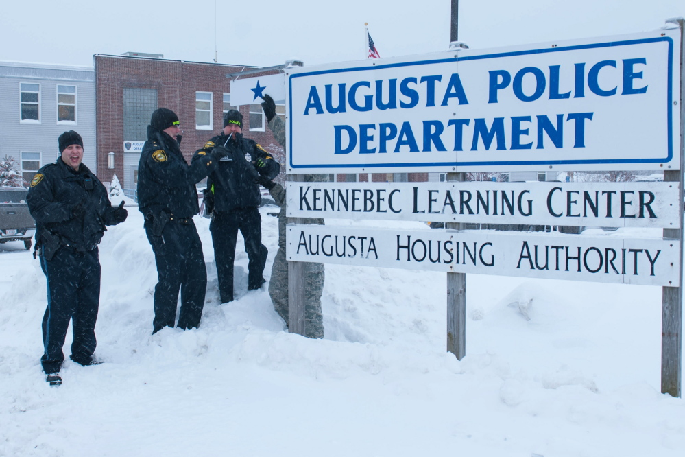 """Augusta Police Department Chief Robert Gregoire, right, and Sgt. Christian Behr, center, hang a blue star beside the Augusta Police Department sign recently to honor patrolman and Air National Guard Staff Sgt. Brad Chase, left, who will deploy with the 101st Security Forces Squadron later this year. A brief ceremony was attended by Brig. Gen. Gerald Bolduc, commander of Maine Air National Guard, and Col. Eric Lind, director of staff, Maine Air National Guard. Behr and Gregoire each spoke to those in attendance. """"He will be missed. He keeps things lively and always gets us laughing first thing in the day. He is an asset to this department,"""" Gregoire said at the ceremony. Chase joined the department in 2011. The star was hung as a sign of unity for the service member and his police department family."""