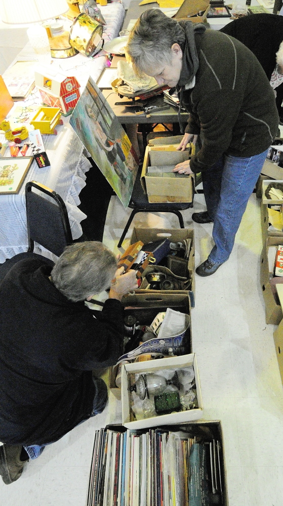 DISCOVERY: Rick Mathiau, bottom, of Vassalboro, shows his wife, Judy Mathiau, something he found in a box during the New Year's Antiques Show on Wednesday at the Augusta State Armory.