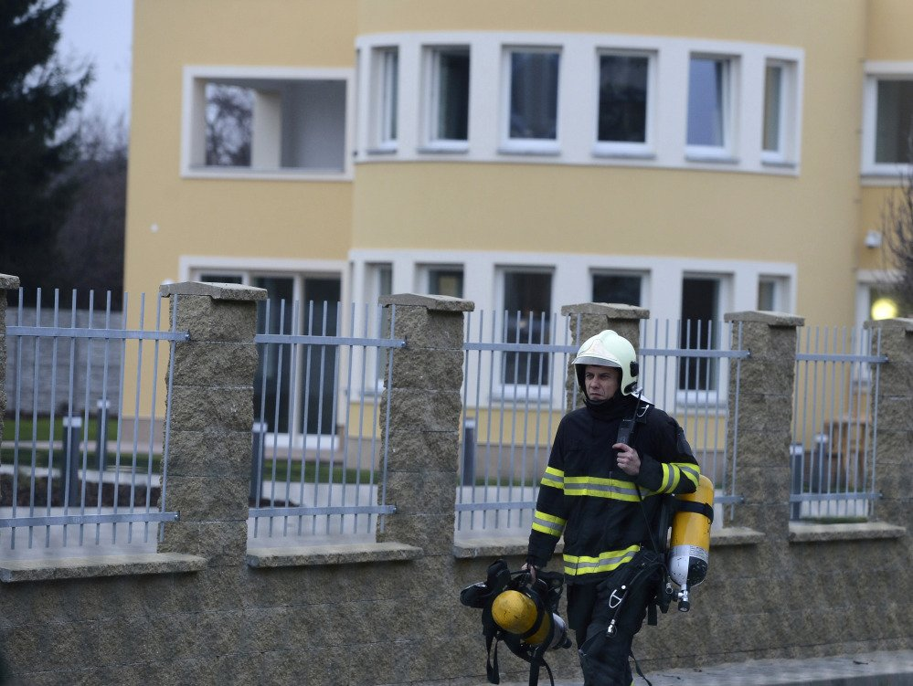 A fireman walks off the residence, back, of Palestinian ambassador to the Czech Republic Jamal Al Jamal, who was killed in an explosion in a diplomatic flat in Prague-Suchdol and was taken to the Central Military Hospital, Wednesday.