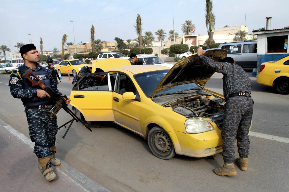 Iraqi federal policemen search a car at a checkpoint in Basra, Iraq's second-largest city, 340 miles (550 kilometers) southeast of Baghdad, Iraq, Thursday, Jan. 2, 2014. The Iraqi government has tightened its security measures after security forces have arrested, Wathiq al-Batat, a controversial Shiite cleric who leads an Iranian-backed militia called Mukhtar Army.