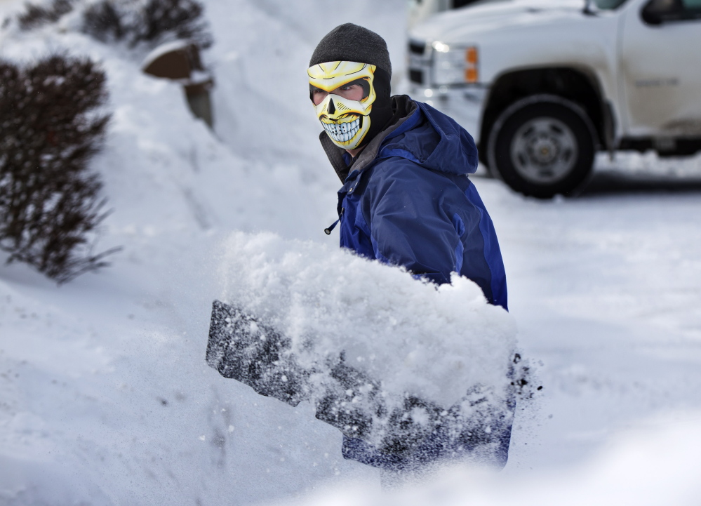 With the temperature at 3 degrees, Drue Ford shovels snow wearing a face mask to guard against frostbite Friday in Brunswick.
