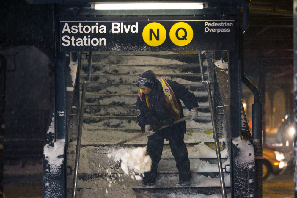 A worker clears snow from a stairway at the Astoria Blvd. subway station Friday in the Queens borough of New York. New York City public schools were closed Friday after up to 7 inches of snow fell by morning.