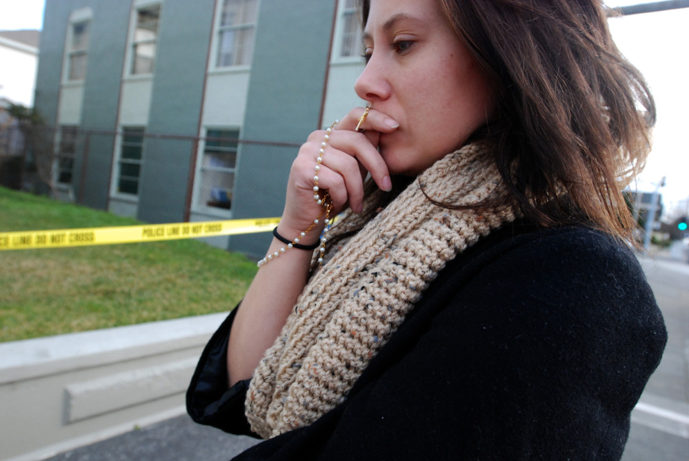 Karli Kauffman of Los Angeles contemplates the death of the Rev. Eric Freed on Thursday outside St. Bernard Catholic Church in Eureka, Calif, where Freed was found slain in the rectory on New Year's Day.