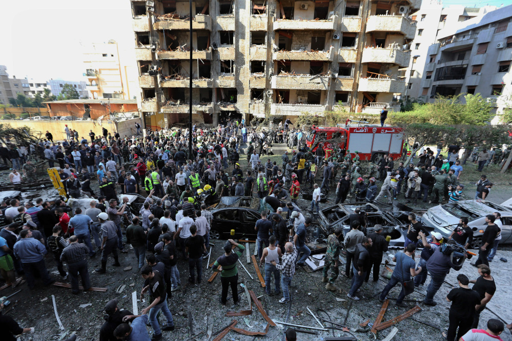 Lebanese people gather at the scene where two explosions have struck near the Iranian Embassy in Beirut, Lebanon. DNA tests confirmed that a man in Lebanese custody is the suspected leader of an al-Qaida-linked group that has claimed responsibility for bombings across the Middle East.