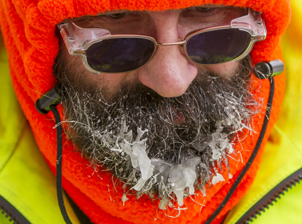 Ice forms on the beard of Bob Schweitzer as he helps clear ice and snow from the seats at Lambeau Field on Friday in Green Bay, Wis., in preparation for Sunday's wild-card playoff game between the Green Bay Packers and San Francisco 49ers.