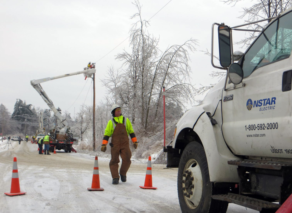 A crew from NSTAR works to restore power in Gardiner on Dec. 26 after the ice storm. Hundreds of utility line crew members and tree trimmers left Maine even as hundreds of customers remained in the dark because Bangor Hydro Electric Co. waved off the extra help.