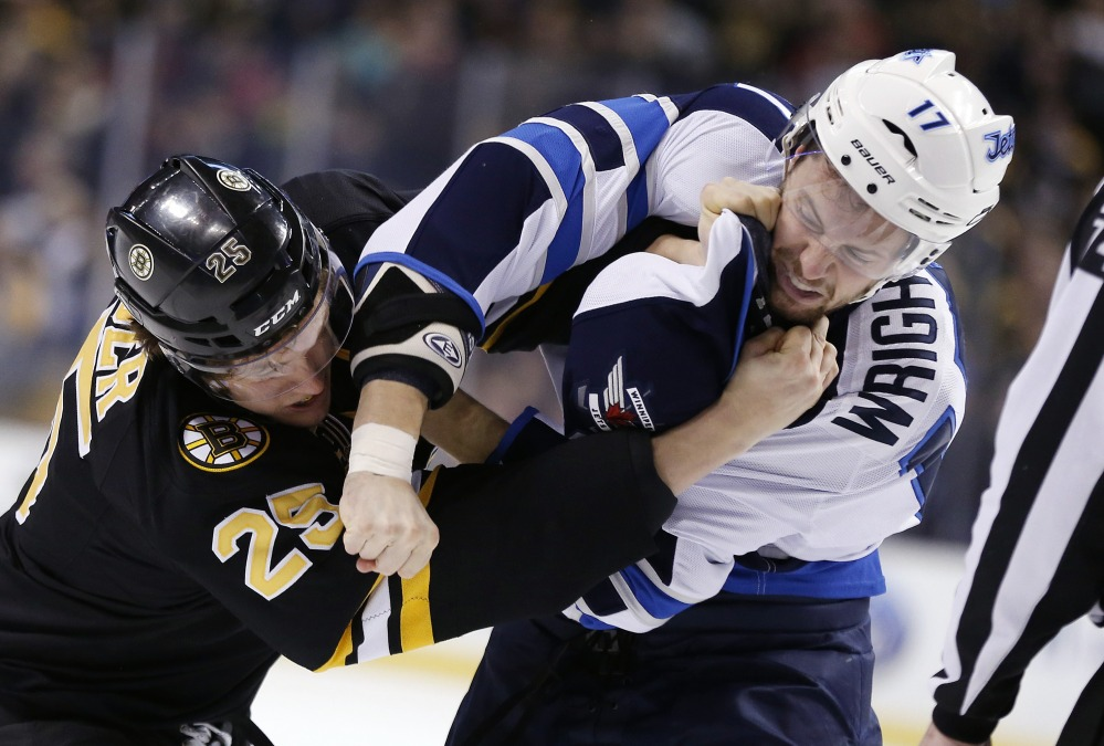 Matt Fraser of the Bruins, left, and Winnipeg's James Wright fight in the first period Saturday in Boston. The Bruins won, 4-1.