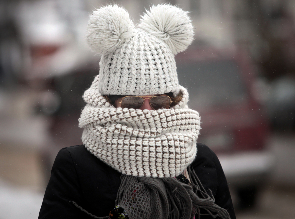 As frigid weather takes hold on the upper Midwest, Kristy Gruley of Madison, Wis., is well-bundled against the elements while walking in the city on Friday.