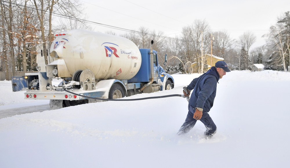 "Staff photo by Michael G. Seamans WINTER HEAT: Greg French, a 15-year veteran delivery man for Dead River Oil, trudges through deep snow to make a delivery on Primrose Street in Winslow on Friday. French said it has been busier than usual compared to previous years. ""We haven't seen cold like this in a long time. Usually there is a bit of relief with a thaw. Not this year,"" French said."