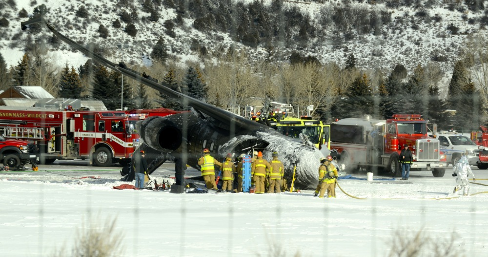 Emergency crews work near a passenger plane that crashed upon landing at the Aspen-Pitkin County Airport in Aspen, Colo., Sunday,