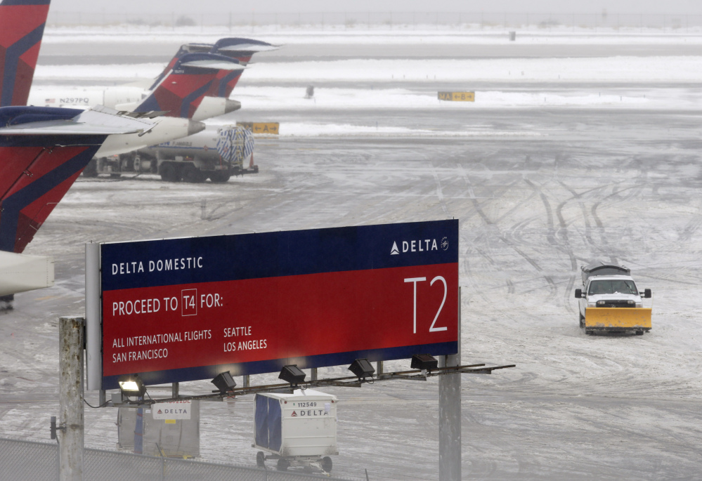 A snowplow makes its way on a slushy patch between two terminals after a Delta flight from Toronto to New York skidded off the runway into snow at Kennedy International Airport, temporarily halting all air travel into and out of the airport on Sunday.