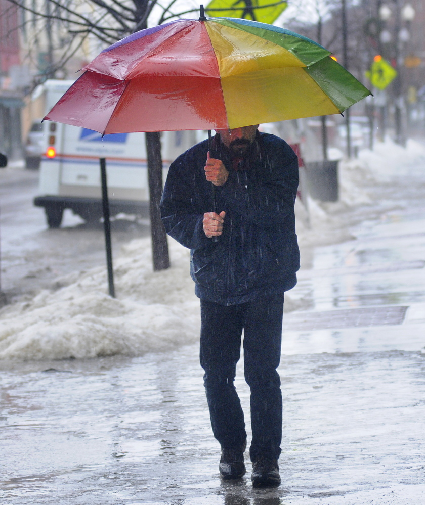 ELEMENTS: Wes Sproul walks over ice Monday on Water Street in Augusta while getting a cup of coffee. Several inches of rain fell on snow and crust, creating hazardous conditions outside.