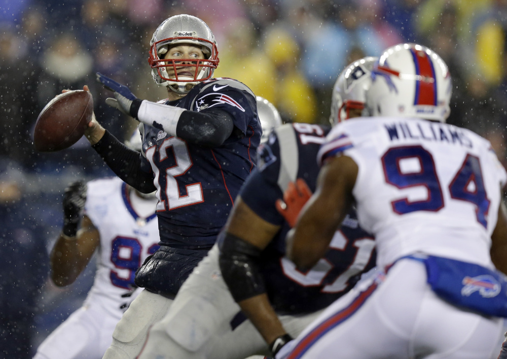 New England Patriots quarterback Tom Brady (12) passes against Buffalo Bills defensive end Mario Williams (94) in the first quarter of an NFL football game, Sunday, Dec. 29, 2013, in Foxborough, Mass. (AP Photo/Steven Senne)