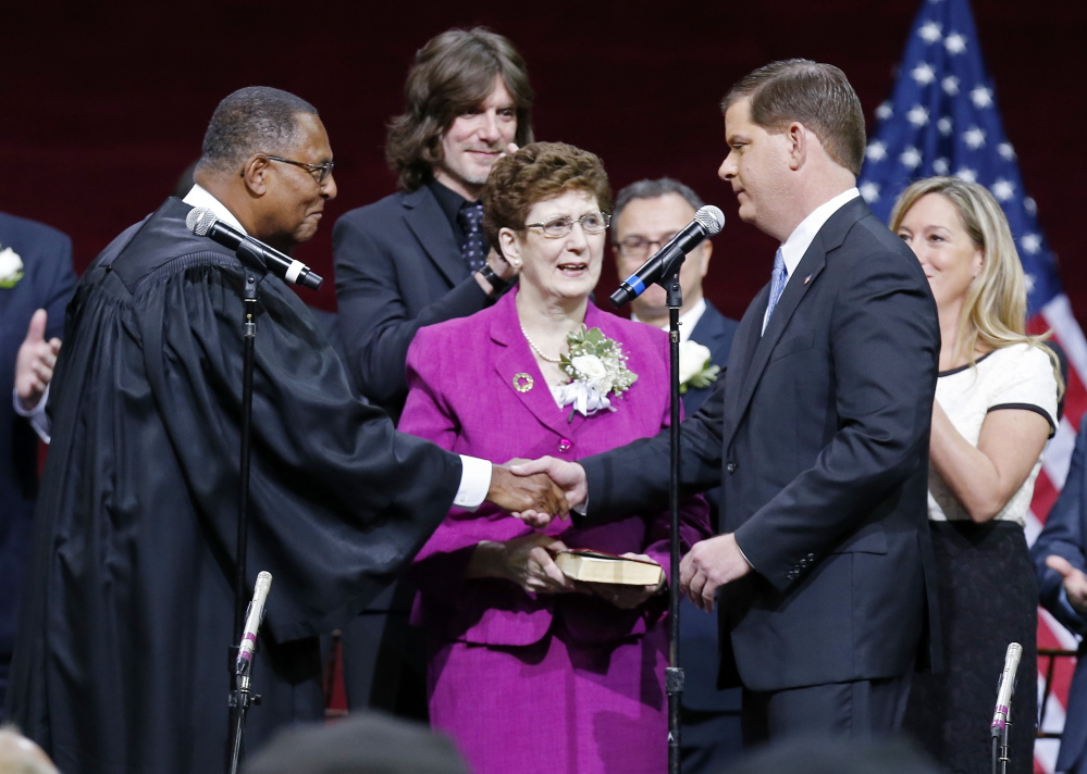 Boston Mayor Marty Walsh, right, shakes hands with Massachusetts Supreme Court Chief Justice Roderick Ireland after taking the oath of office in Conte Forum at Boston College on Monday.
