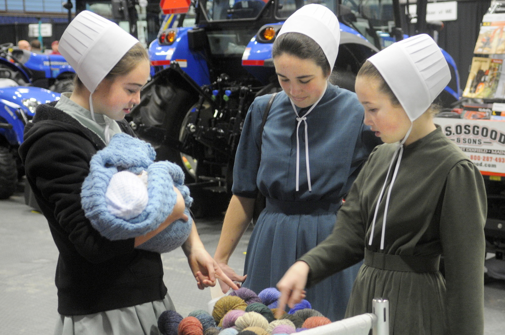 AGRICULTURE: Lilia, left, Cassia and Moriah Higgins inspect yarn Tuesday on display on the first day of the Maine Agricultural Trades Show at the Augusta Civic Center. Several thousand people were expected to attend the annual event for Maine farmers. The Higgins sisters raise sheep and pygmy goats at Fruitful Acres Farm in Newport. Lilia is holding family friend Naphtali Kulp, 1 month old.