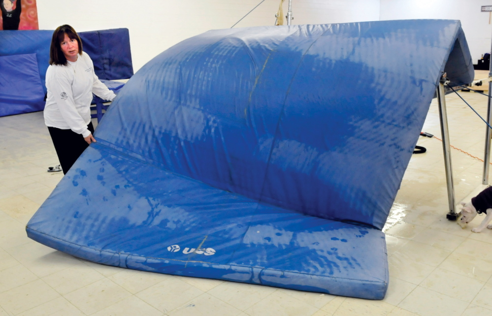 Staff photo by David Leaming UNWELCOME SURPRISE: Carol Hamilton, co-owner of Decal Gymnastics in Farmington, holds a water-soaked mat used at the facility on Tuesday. Hamilton said water from the roof entered the building and soaked flooring, carpets, mats and dance equipment Monday evening. She said she hopes to reopen in a month.