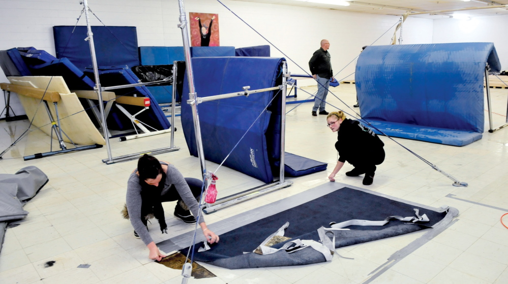 Staff photo by David Leaming REPAIR: Decal Gymnastics co-owner Delani Evans, left, employee Whitney Blanchet and volunteer Dennis Hanson, in background, remove items from the water-soaked floor of the Farmington business on Tuesda. Water from the roof soaked the spring floor, mats, carpets and foam pads on Monday evening.